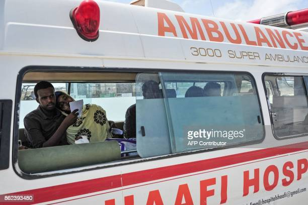 A Somali woman severely wounded by a truck bomb explosion three days prior leans on her husband before being transferred to an aircraft from an...