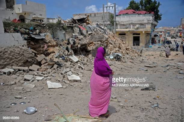 A Somali woman stands amid rubble after two car bombs were detonated and three Shabaab gunmen were shot dead after exchanging fire with security...