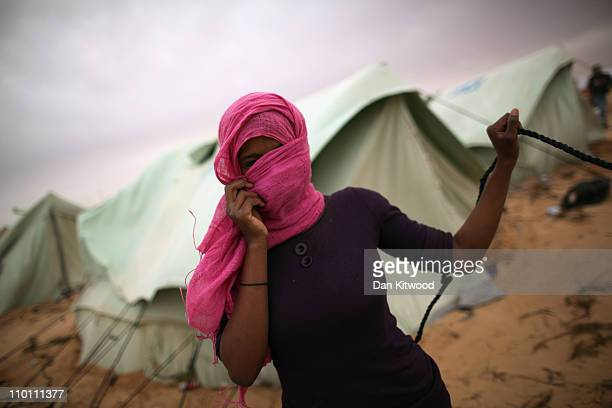 Somali woman ties down her tent during a sandstorm at a United Nations displacement camp during a sandstorm on March 15 2011 in Ras Jdir Tunisia As...