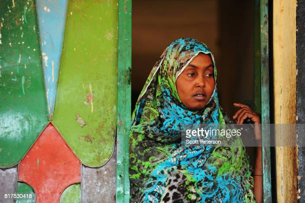 Somali woman watches as villagers who have benefited from food and cash donations mobilized by a WhatsApp group called Daryeel formed by diaspora...