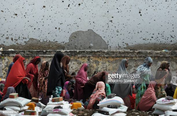 Somali women walk underneath a bullet scarred wall once used as a cinema screen to collect sacks of rice flour and sugar donated to them and other...