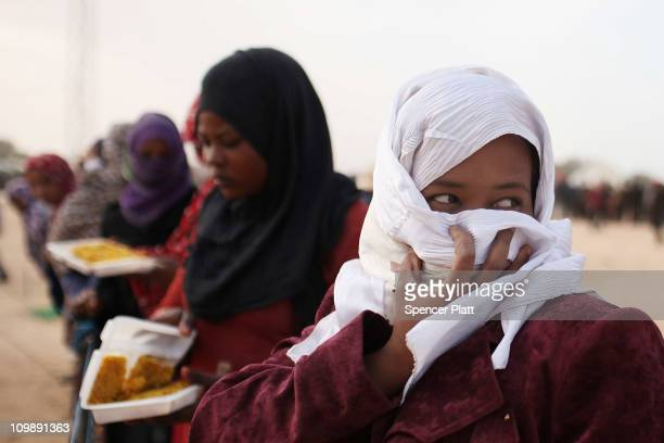 Somali women who recently crossed into Tunisia from Libya wait for food outside of a feeding center in a United Nations sponsored displacement camp...