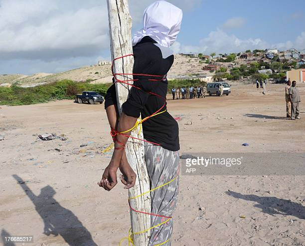 Somalia convicted murderer Adan Sheikh Abdi is tied to a post before being executed on August 17 2013 by a firing squad in a Mogadishu square for the...