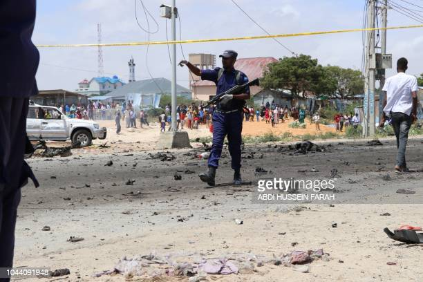 A Somalia police officer secures the scene of a suicide bomb attack in the capital Mogadishu on October 1 2018 after a suicide bomber rammed a...