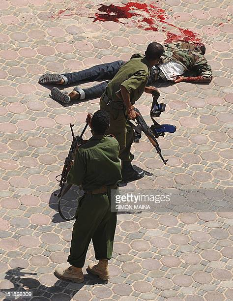 Somalia policemen walk away from the body of one of the suicide bombers who was killed as he attempted to enter the hotel Jazeera compound in...