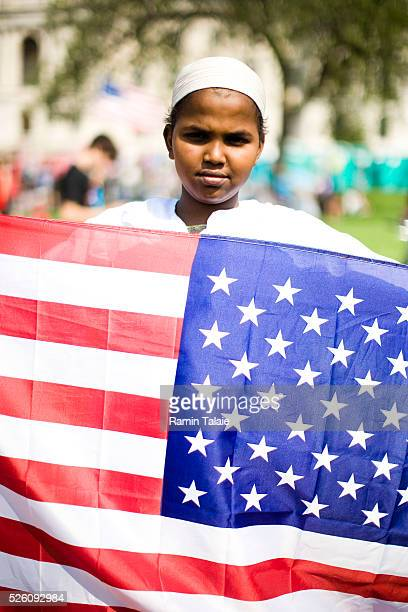 A Somalian boy Ahmad Mohamud of Minneapolis holds an American flag during protests on the first day of the Republican National Convention at the Xcel...