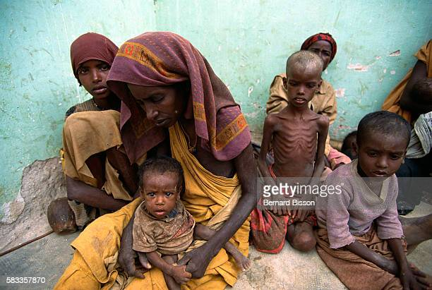 Somalian children and mothers sit and kneel on the ground with their faces and bodies bearing the obvious marks of starvation They have been in this...