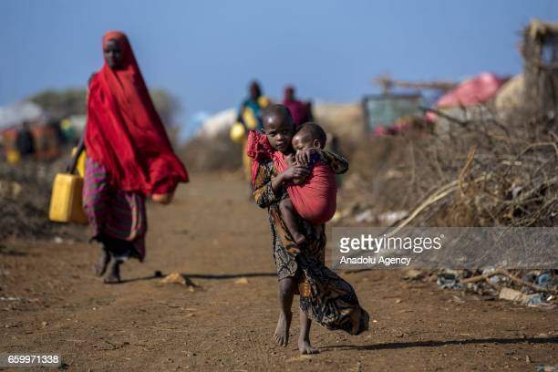 Somalian girl carries her sibling at the Mooro Hagar camp in the Somalia's Bay state on March 29 2017 In the central and south parts of Somalia...