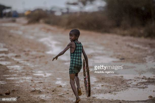 Somalian kid plays with an old bicycle rim during a short time period rainfall in Baidoa city of Somalia's Bay state on April 05, 2017. In the...