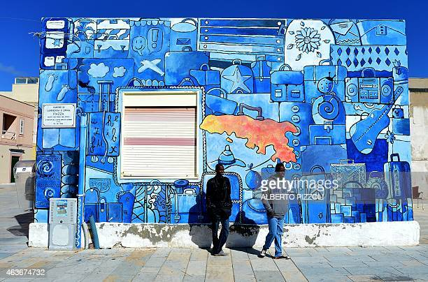 Somalian migrants Mohmoud and Abdinajib on February 17 pose in front of a mural in a street of Lampedusa a day after being rescued at sea They...