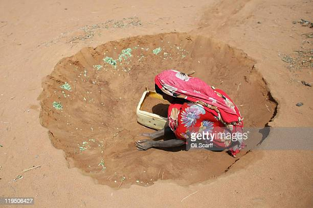 Somalian refugee collects sand outside her hut to act as building material on the edge of the Dagahaley refugee camp which makes up part of the giant...