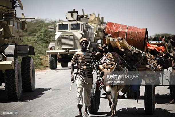 Somalian refugees from the al Shabaab-controlled town of Afgooye pass AMISOM vehicles along a road on February 20, 2012 in Mogadishu, Somalia. As...