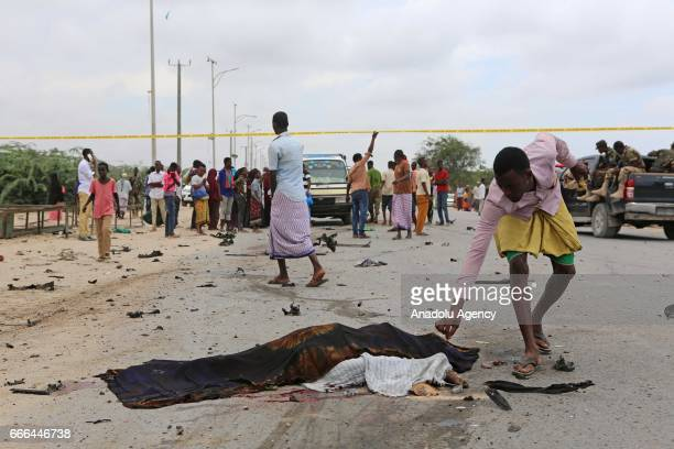 Somalian security forces and people gather at a scene after a bomb attack targeting the Armed Forces Command near the Defense Ministry in Mogadishu,...