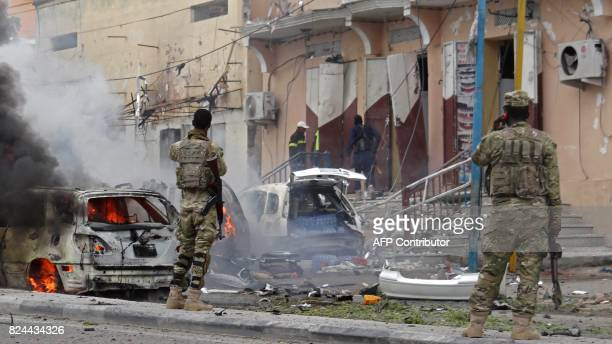 Somalian security personnel look towards burning vehicles as they secure an area in Mogadishu on July 30 after a car bomb explosion in the Somalian...