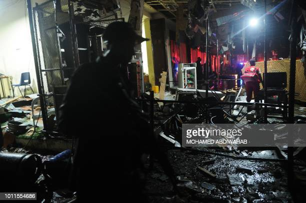 A Somalian soldier and an emergency responder walk at the site of a car bomb explosion in Mogadishu on August5 2018 At least three were killed and...