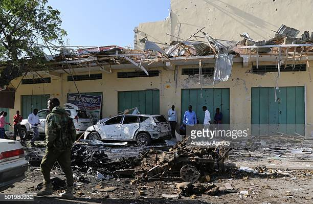 Somalians are seen in front of damaged building after an assassination attempt to governor in Mogadishu Somalia on December 19 2015 7 people injured...