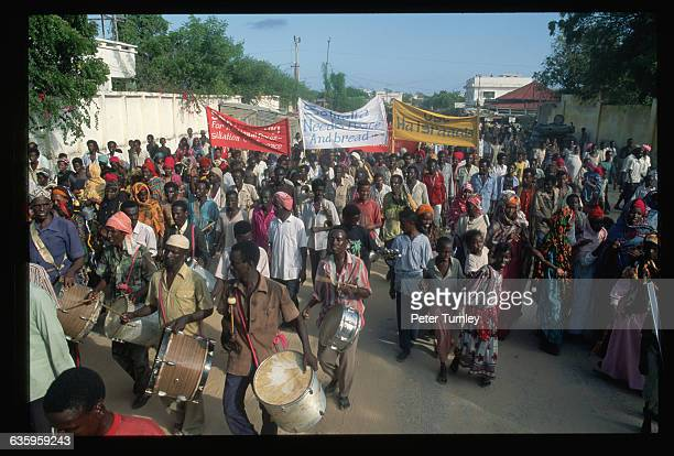 Somalis carry banners and beat drums during a peace demonstration in front of General Mohammed Farah Aideed's house to welcome the arriving troops In...