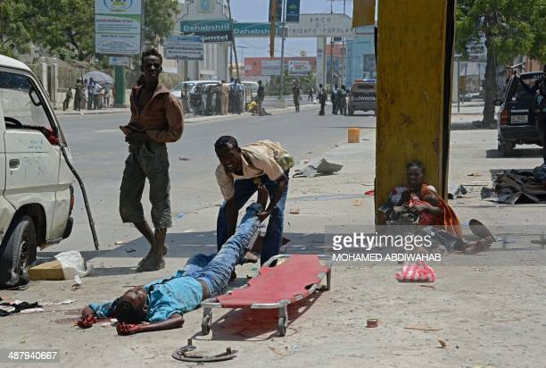 Somalis help carrying a blast victim onto a stretcher as a wounded Somali mother holds her two children one wounded and one dead after a huge...