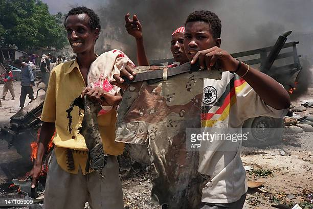 Somalis hold a pair of camouflage trousers 03 October 1993 in a Mogadishu street claimed to be from a US soldier killed during clashes with...