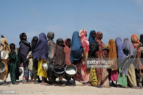 Somali's hold pots as they wait in line to receive a hot meal at a food distribution point in Somalia's capital Mogadishu on August 18 2011 Over...