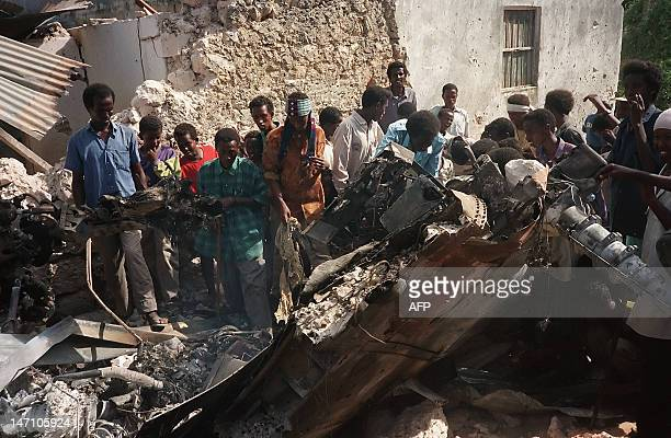 Somalis look at the wreckage of a US helicopter in a Mogadishu street 04 October 1993 after it was shot down Twelve soldiers were killed 76 wounded...