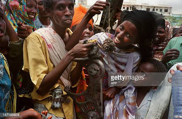 Somalis pose in a Mogadishu street 04 October 1993 with what they claim to be the remains of a US soldier killed 03 October during a battle with...