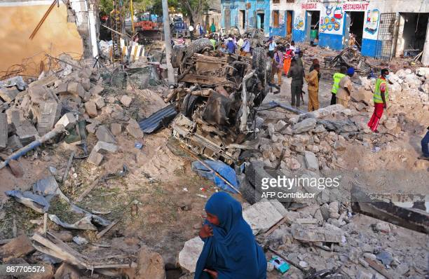 Somalis security forces and local residents walk at the scene of a blast on October 29 a day after two car bombs exploded in Mogadishu Somalia's...
