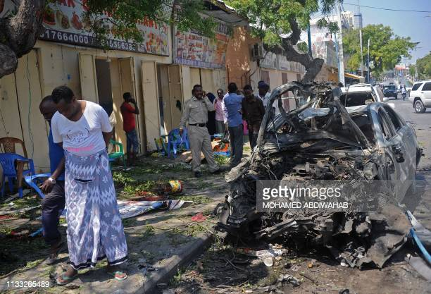Somalis stand at the site of an explosion outside a restaurant in Mogadishu on March 28 2019 A large bomb exploded in Somalia's capital Mogadishu on...
