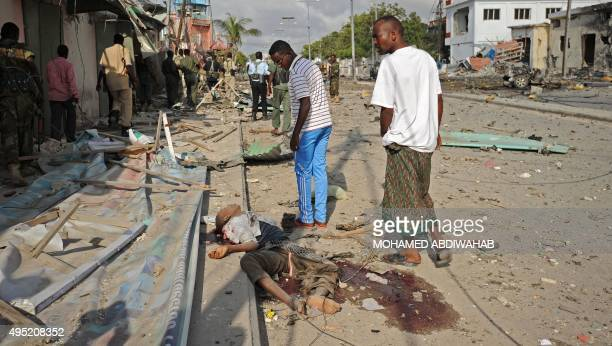 Somalis stand over a body after an explosion on November 1 2015 near the damaged Sahafi hotel in Mogadishu At least 12 people were killed in the...