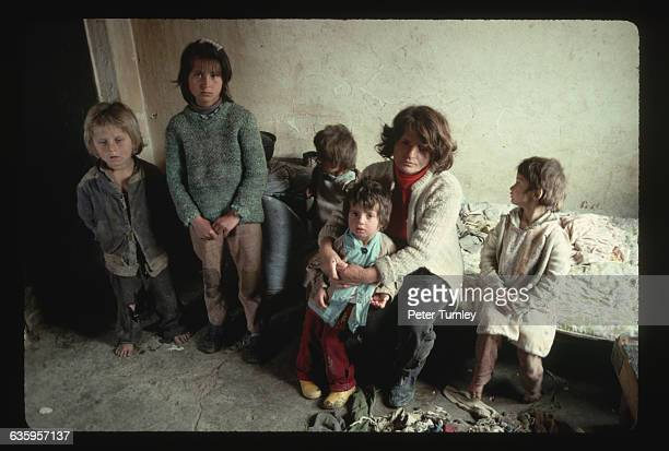 A somber Albanian family sits together in a dingy room in Albania's capitol city