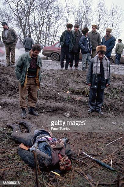 Somber Chechens stand near the body of a man killed during the fighting between Chechen rebels and Russian troops