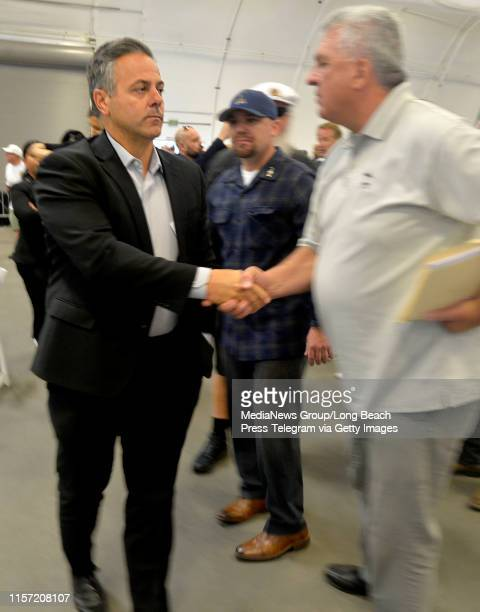 A somber looking LA City Councilman Joe Buscaino shakes hands with ILWU local 13 president as he exits the Harbor Commission meeting in San Pedro on...