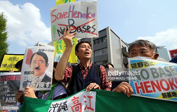 Some 100 antiUS base activists shout slogans as they protest against the construction of the new base in Okinawa during a rally in front of the prime...