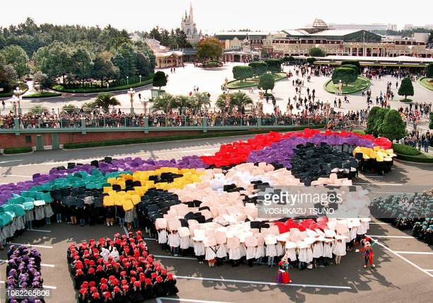 Some 2300 guests raise the color boards over their heads to form a colorful face of Mickey Mouse to celebrate the famous Disney character's 70th...