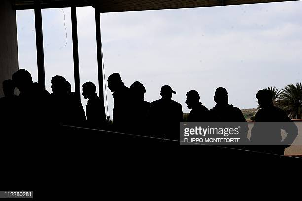 Some 30 Tunisian migrants who will be sent back to Tunisia arrive at the Lampedusa airport, on April 11, 2011. Around 26,000 undocumented migrants...