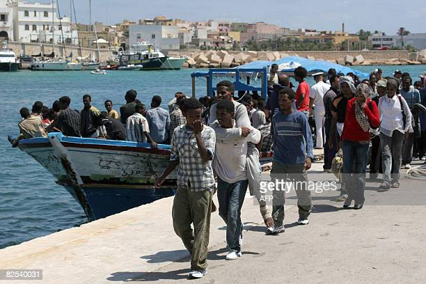 Some 355 wouldbe immigrants from Eritrea disembark on arrival by boat in the port of Italy's southern island of Lampedusa late on 21 August 2008...