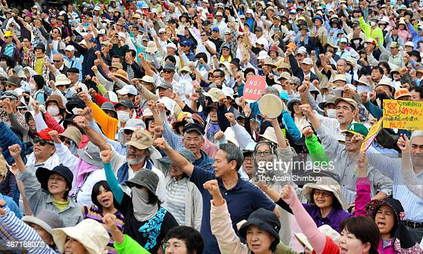 Some 3900 antiUS air base relocation protesters raise their fists during a rally at Sedake beach on March 21 2015 in Nago Okinawa Japan Japanese...
