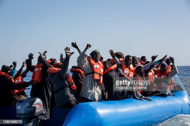 Some 47 migrants aboard an unflatable boat react after learning that they are being rescued by the Dutch-flagged Sea Watch 3 off Libya's coasts on...