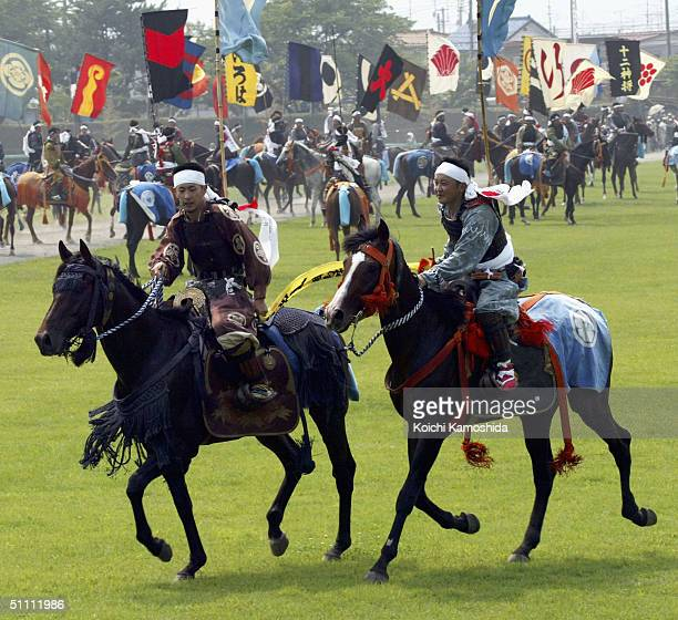 Some 600 horsemen in samurai costumes scramble for shrine flags as part of an equestrian contest during the Soma-Nomaoi festival on July 24, 2004 in...