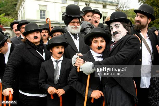 Some 662 people dressed as 'The Tramp' pose for a group picture to mark the first anniversary of Chaplins World By Grevin and Charlie Chaplins...