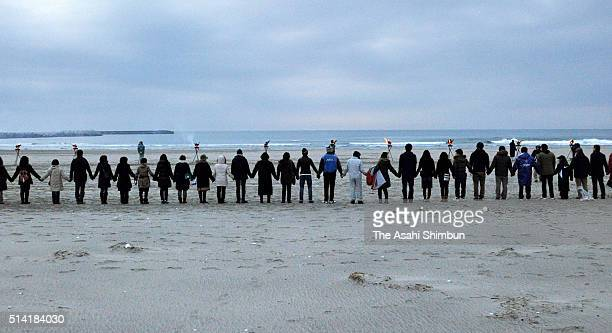 Some 800 people holding their hands in line toward the sea pray for the victims and hope for reconstruction ahead of the fifth anniversary of the...