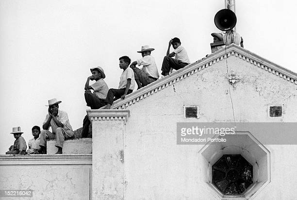 Some Argentinian men sitting in a line on the roof of a building Buenos Aires August 1970