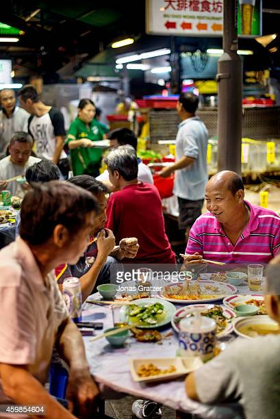 Some Asian men feasting around a table at a street food stall in the city of Hong Kong