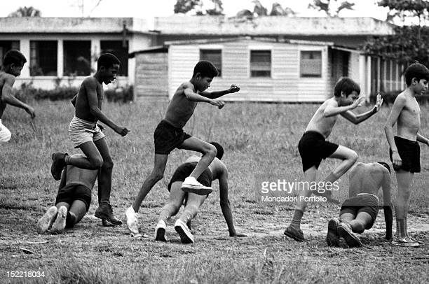 Some barechested boys are exercising outdoor Latin America 1970