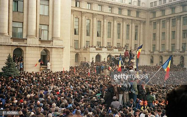 Some Bucharest citizens wave Romanian flags amongst thousands as they stage an anticommunist demonstration at the Republic Square 21 December 1989 in...