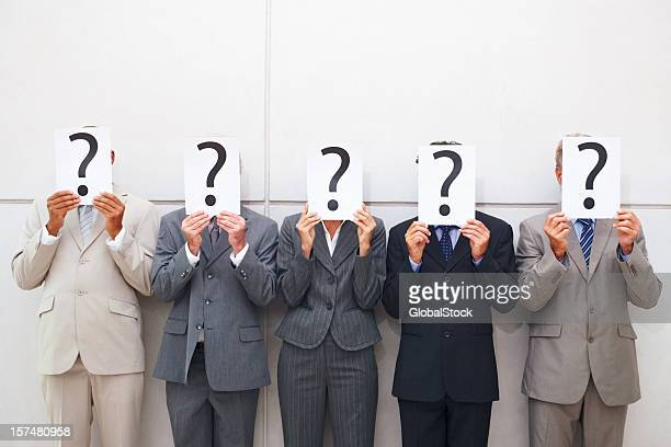 some businessmen cover their faces with a question mark sign - five people stock pictures, royalty-free photos & images