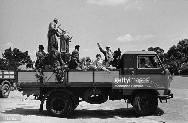 Some children carrying a statue of Saint Joseph on a lorry on 10th May Agrigento 1950s