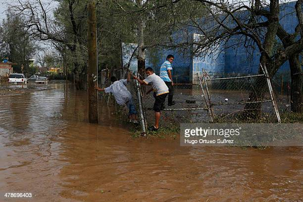 Some children climb a metallic fence on a sidewalk flooded by heavy rains left by the waterspout recorded in Teuchitlan City, Mexico. At least 90...