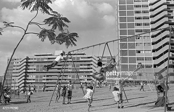 'Some children having fun on the swings in front of some buildings Caracas January 1958 '