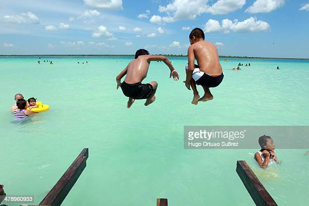 Some children jump into the water from the dock of the 'Lagoon of Seven Colours' Located in the north of the city of Chetumal just 35 miles away the...